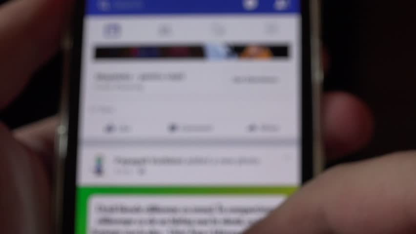 Closeup smart phone online social media facebook browsing news feed blur friends | Shutterstock HD Video #15495961