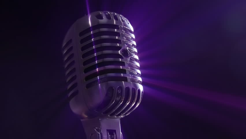 Shure 55SH Series II Iconic Unidyne Vocal Microphone (The Elvis Microphone), rotating as it reflects blue and purple stage lighting.