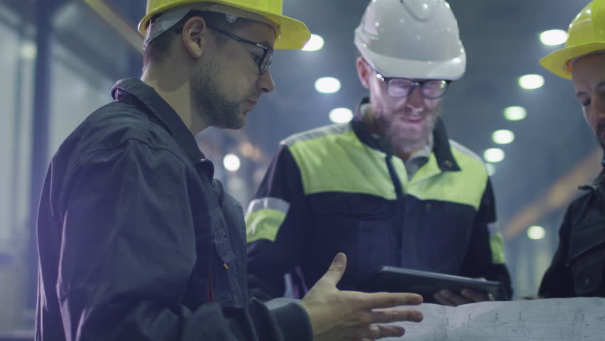 Team of workers at a heavy industry factory have a conversation while looking at a blueprint. Shot on RED Cinema Camera.