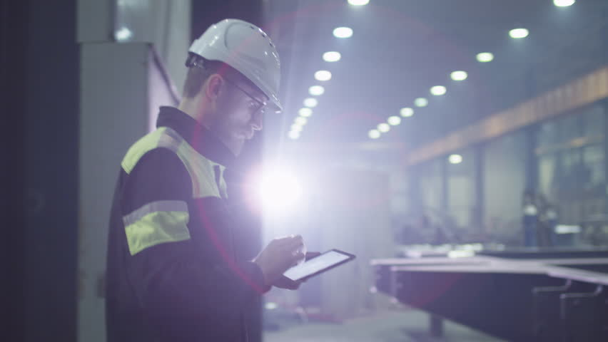 Engineer in hardhat is moving through a heavy industry factory with a tablet computer. Is greeting a worker with a handshake. Shot on RED Cinema Camera.