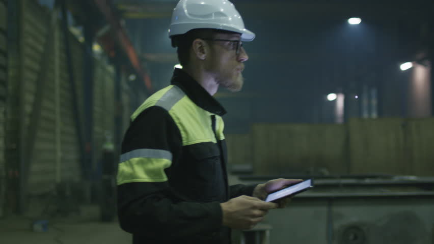 Engineer in hardhat is moving through a heavy industry factory with a tablet computer. Shot on RED Cinema Camera. | Shutterstock Video #15514930