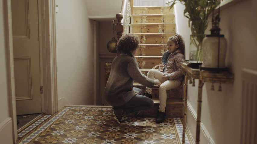 Mother preparing daughter for school at home