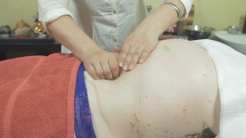 Masseuse make massage of fat stomach to adult woman in professional saloon.  Tingling. Medium shot