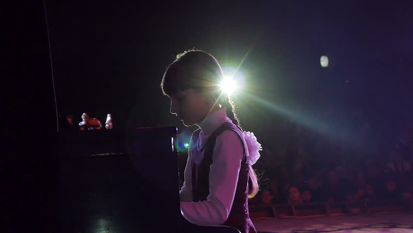 A young girl playing the piano at the theater