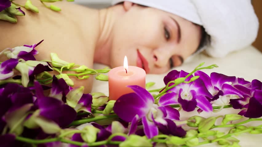 View face and back woman lying near flowers and with candle in beauty salon. #15534751