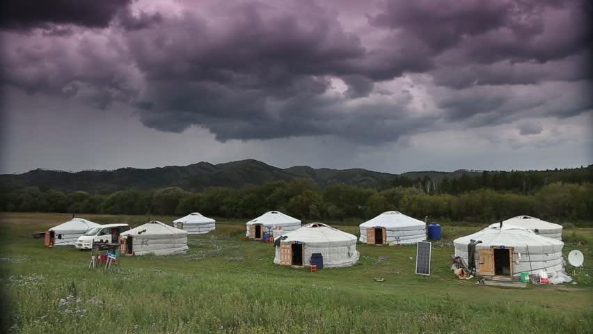 Timelapse of Mongolian Ger or Yurt camp with menacing storm clouds with background of green hills.