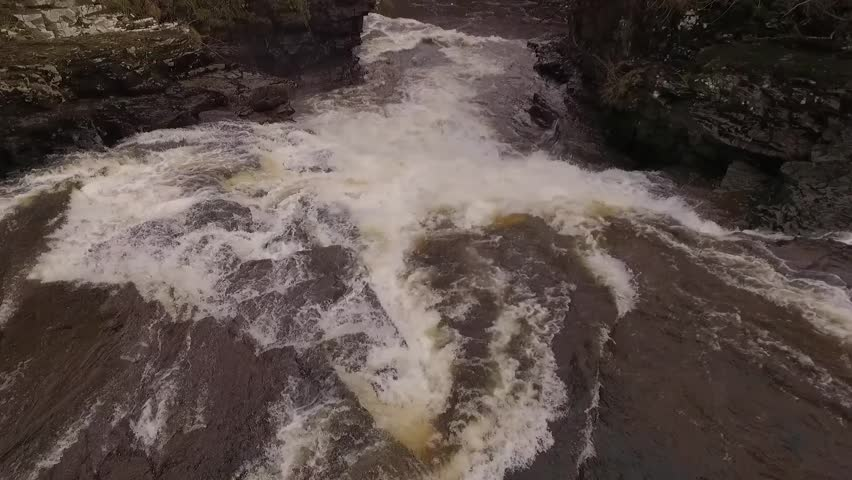 Aerial low flyover of a heavy flowing brown waterfall in Scotland