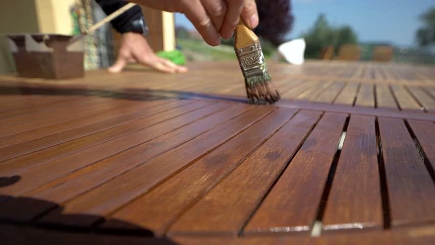 Macro shot of restorer restoring a wooden table varnishing with a mordant. Garden furniture.
