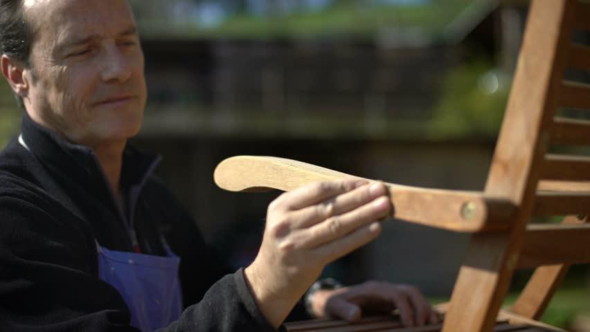 Closeup of handsome carpenter restoring a wooden chair with sandpaper. Garden furniture.