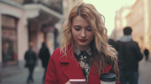 Business woman in red coat with coffee walking in the city and communicate via smart phone (phablet) steady cam shot