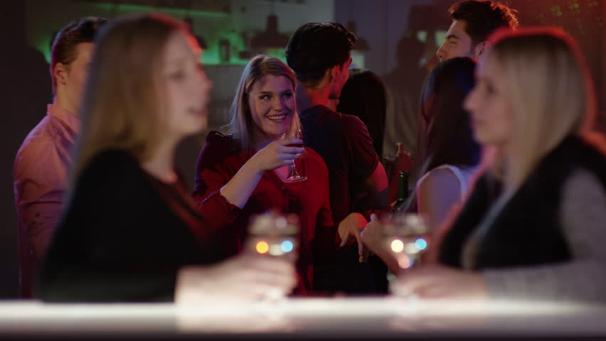 Two attractive girls at bar in club talking and raising their glasses | Shutterstock HD Video #15565951