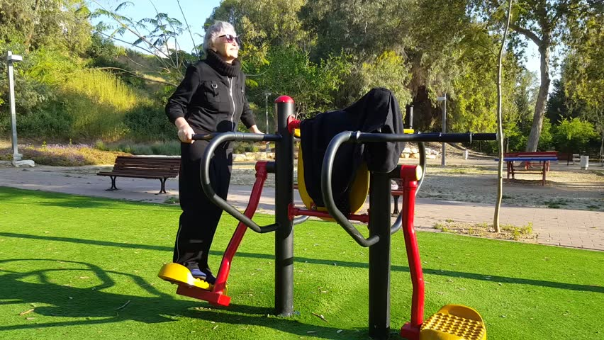 76-year-old woman tries out surf fitness machine in her local park. Grey-haired woman in black sport suit is working out at outdoor gym. Promote health and well-being lifestyle concept.