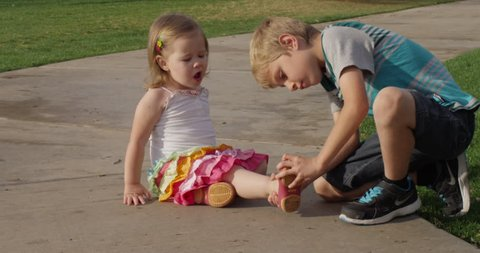 RED 2K slow motion shot of a brother helping his sister with her shoe on a walkway in a park.