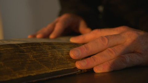 Monk's Hands Are Holding, Monk is Reading an Old Book in a Typography, Touching a Yellow Pages of Ancient Slavic Manuscript in the Light of Candle in Dark Room, Tale of Bygone Years, Primary