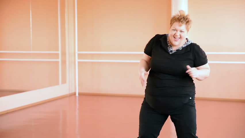 overweight girl is engaged in dances in the hall. cheerful plump, gymnastics and dance