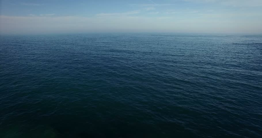 Aerial view, dolly in of calm, blue sea. Slow motion. #15619201