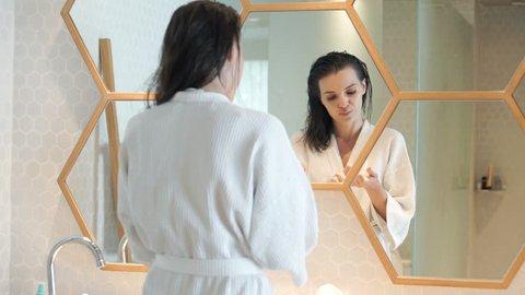 Young, pretty woman in bathrobe applying cream on face and neck in bathroom