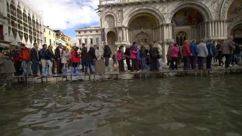 VENICE, ITALY - OCTOBER 15, 2015: Sea level rise - Venice raised paths, boards, passerelle, at high water. Climate Change - Rising ocean levels - high tide flooding.