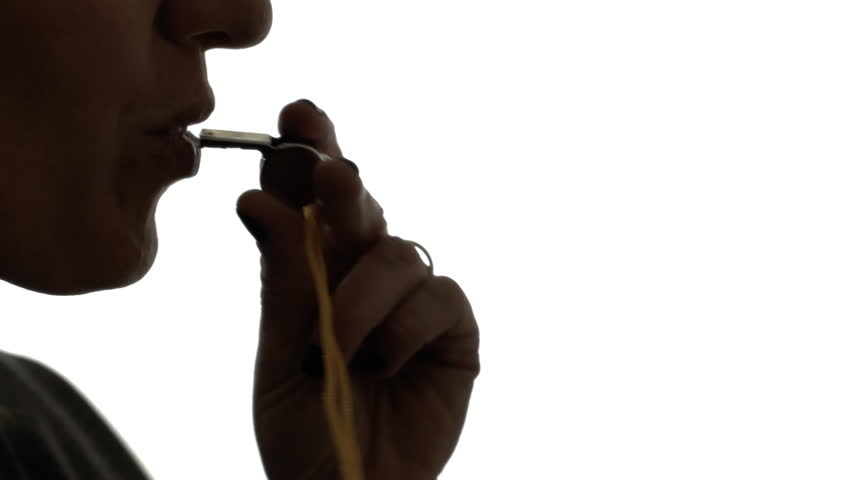 A woman blowing into a whistle. Clear silhouette shot.