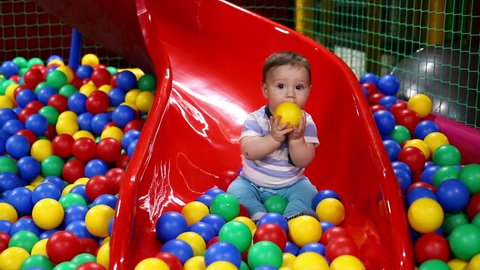 Baby on the chute with balls in playground