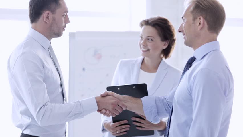 business handshake - two businessmen shaking their hands
