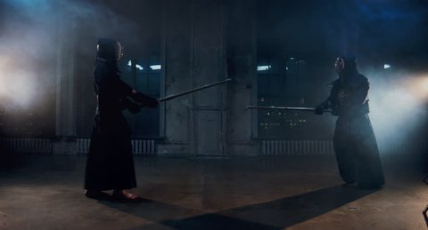 Japanese kendo fighters with bamboo swords competing in the fog.