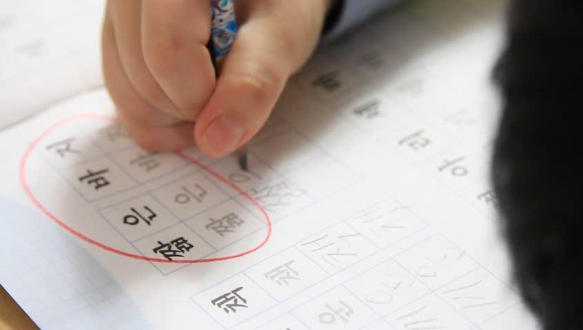 Pan left shot of little kid learning to write Korean letters