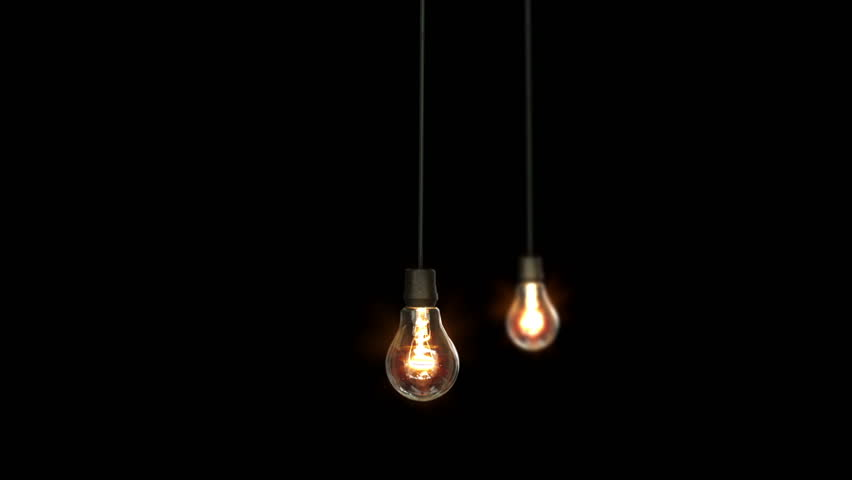 2 light bulbs hanging over a black background hd stock video clip