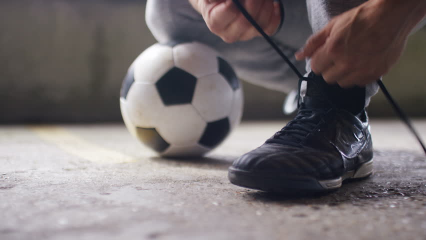4K Young footballer tying his laces in urban environment, in slow motion