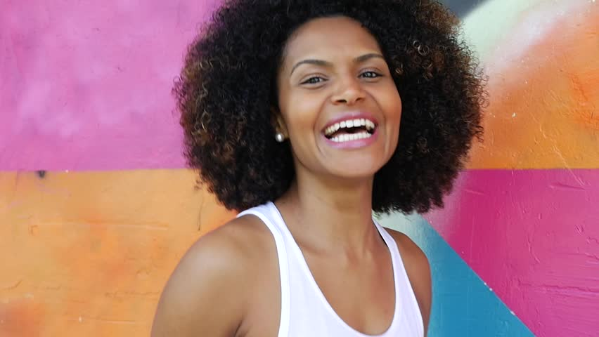 Young latina smiling on colorful background