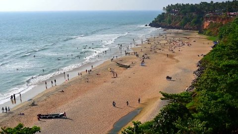 Varkala Beach (Kerala, India). Distant view of blue sea, waves, sand and tourists