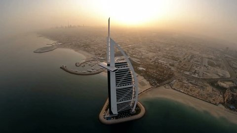 DUBAI, UAE - SEPTEMBER 14: Fly over Burj Al Arab hotel in Dubai, UAE. Burj Al Arab is a luxury 5 star hotel built on an artificial island in front of Jumeirah beach. Helicopter aerial view at sunrise
