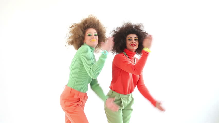 Two funny girls wearing a 70s retro clothes dancing in studio. Disco diva over white background
