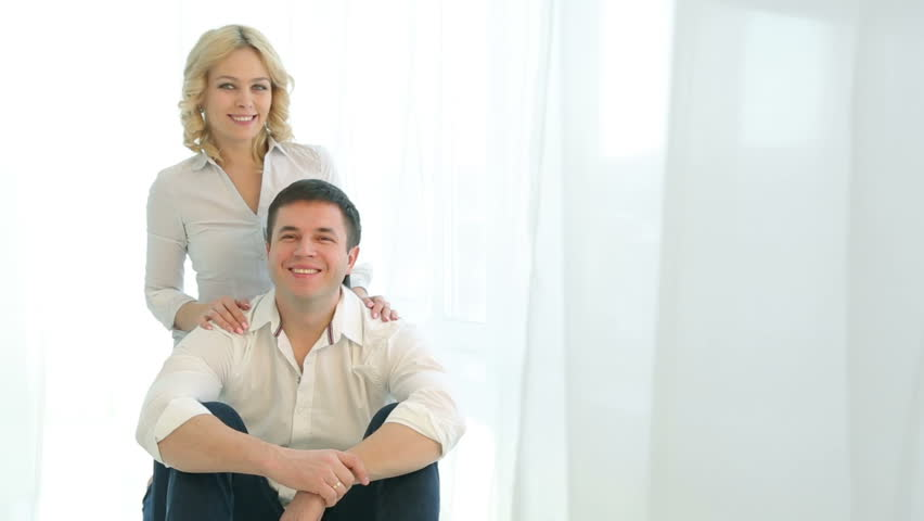 Husband and wife sitting on the floor next to each other near a large window, they hug, looking at the camera.Happy family in white shirts and jeans. Man and woman smiling, hugging.