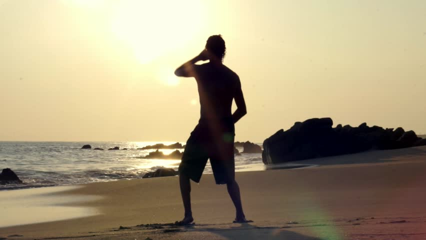 Caucasian man practicing tai chi on the beach at sunset | Shutterstock HD Video #15777811