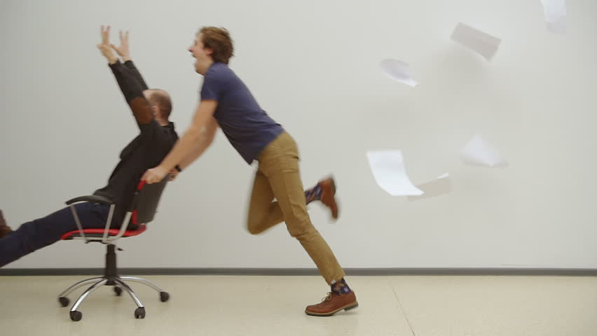 Office chair race. Slow motion. Young guys have fun in the office during a break. Games of businessmen from large offices. Men celebrate a successful deal and throwing papers up. Office party. | Shutterstock HD Video #15778039