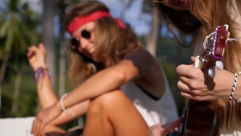 Young Hipster or Hippie Girls Playing Ukulele Outdoors