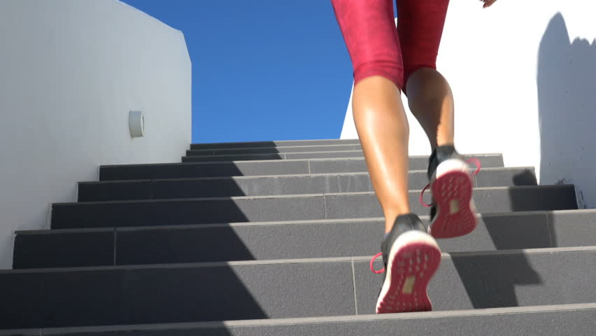 Running on stairs woman doing run up on staircase. Female runner athlete climbing stairs in sport workout run outside. Running shoes and legs close up and zoom in.