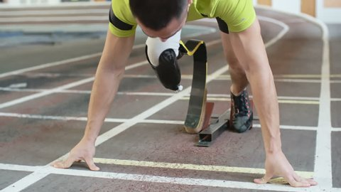 Young athlete with artificial leg starting from blocks on track in slow motion
