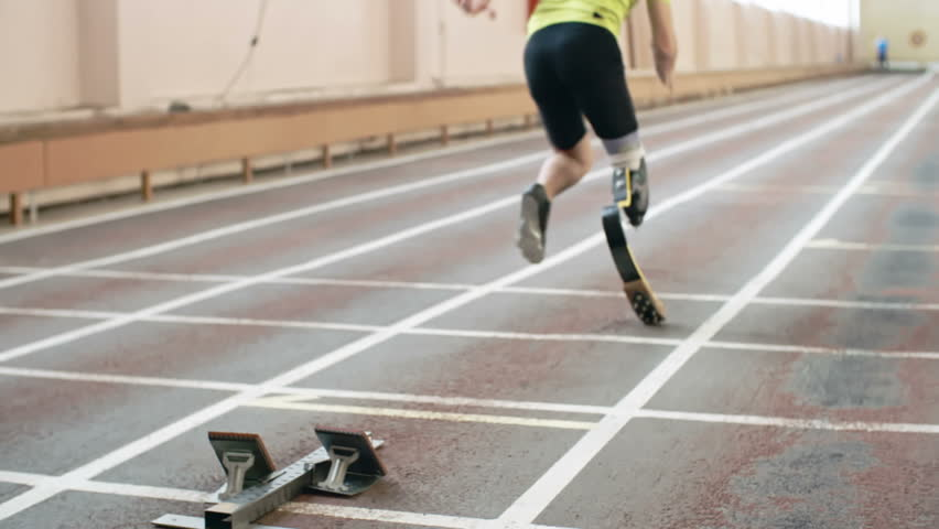 Rear view of athlete with artificial leg starting from blocks in slow motion