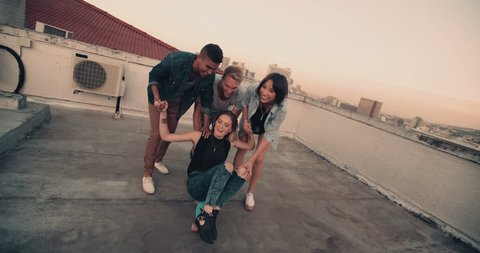 Girl is being pushed on skateboard on the rooftop by a group of friends