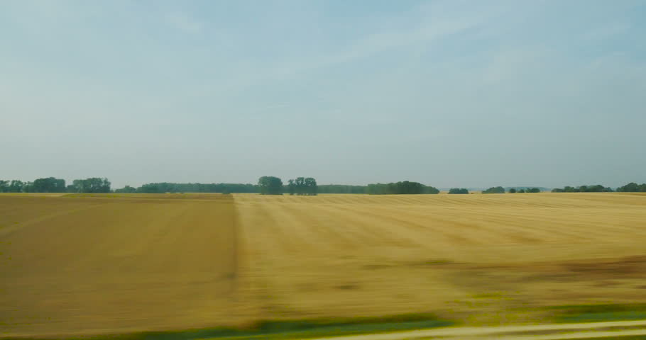 Wheat field cultivated in central France seen from the high speed TGV French train on a beautiful summer day