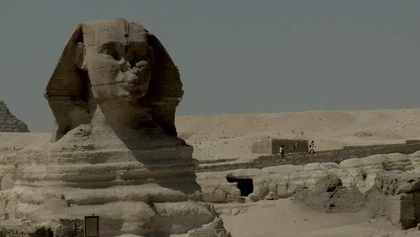 Long shot of head of Great Sphinx, tourist walking on base.