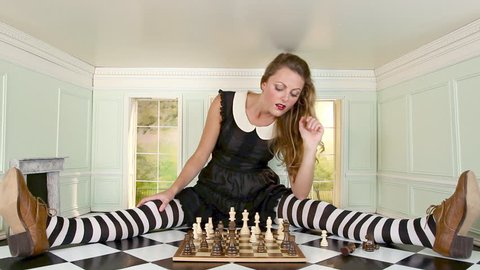 November 12, 2010: Young woman playing chess in small room, zoom in