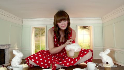 November 12, 2010: Young woman having tea party in a small room