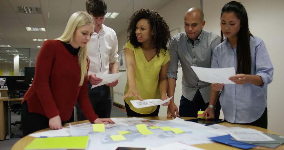 An African American team leader discussing future business ventures with colleagues while looking at a world map. In slow motion. | Shutterstock HD Video #15927991
