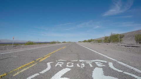 Route 66 old rustic pavement sign driving shot near Barstow, California.