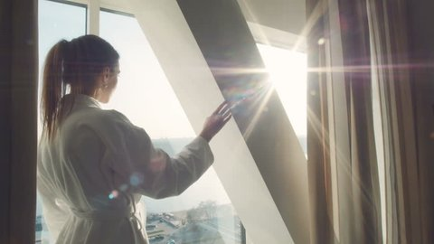 The attractive female approaches a window, and opens curtains at a window in luxury apartments in hotel