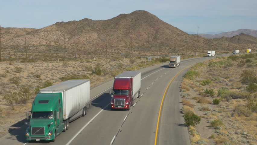 4K AERIAL SLOW MOTION CLOSE UP: Cars and trucks driving on busy highway through the desert. Freight semi trucks transporting goods, personal cars on a road trip, people traveling in sunny summer #15954127