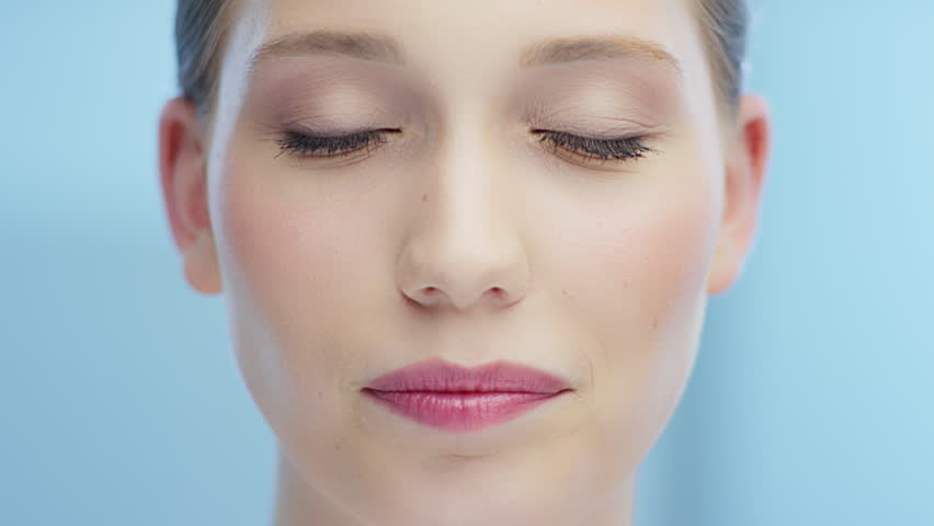 Attractive young woman opens her eyes and smiles | Shutterstock HD Video #15962011